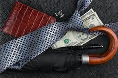Lien, parapluie, stylo, portefeuille, boutons de manchette, argent se trouvant sur la peau Photos stock