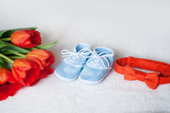 Lien rouge de tulipes et bottes bleues d'enfants sur le fond blanc Image libre de droits