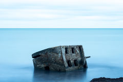 Liepaja beach bunker. Brick house, soft water, waves and rocks. Abandoned military ruins facilities in a stormy sea. Barracks building in the Baltic sea Stock Image