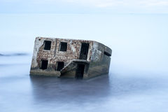 Liepaja beach bunker. Brick house, soft water, waves and rocks. Abandoned military ruins facilities in a stormy sea. Barracks building in the Baltic sea Royalty Free Stock Images