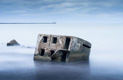 Liepaja beach bunker. Brick house, soft water, waves and rocks. Abandoned military ruins facilities in a stormy sea. Royalty Free Stock Photography