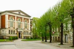 Liepaja-Hochschulgebäude und -straße mit grünen Bäumen Lizenzfreies Stockfoto