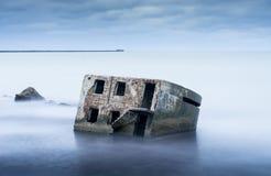 Liepaja-Strandbunker Backsteinhaus, weiches Wasser, Wellen und Felsen Verlassenes Militär ruiniert Anlagen in einem stürmischen M Lizenzfreie Stockfotografie