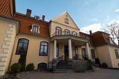 LIEPUPE,拉脱维亚- 2019年4月13日:美好的晴朗的春天天气的Liepupes Muiza庄园与天空蔚蓝和云彩 免版税库存图片