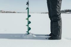 lies för fiskeis bara blockerade vinterzander Drillborr för att borra is, metspöet för vinterfiske och fisken på isen av sjön Fotografering för Bildbyråer
