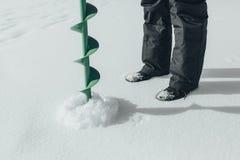 lies för fiskeis bara blockerade vinterzander Drillborr för att borra is, metspöet för vinterfiske och fisken på isen av sjön Royaltyfri Bild