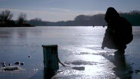 lies för fiskeis bara blockerade vinterzander Fiskare på en sjö på den soliga dagen för vinter lager videofilmer