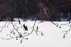 lies för fiskeis bara blockerade vinterzander Flod sjö nära skog i is Suddig bild av sportfiskare, Fishermens till och med trädfi Royaltyfria Foton
