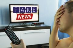 Lies of tv propaganda mainstream media disinformation,. A fake news report. viewer is watching TV and doesn`t believe in fake news. man closes his eyes not to stock photography