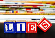 Lies word. Near many newspapers Stock Image