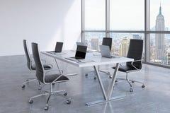 Lieu de réunion moderne avec les fenêtres énormes regardant New York City Chaises en cuir noires et une table blanche avec des or Image stock