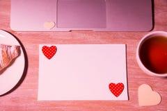 Lieu de travail à la maison espace de travail féminin de bureau avec l'ordinateur portable, le thé et le croissant Vue supérieure Image stock