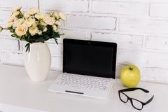 Lieu de travail avec l'ordinateur portable moderne au-dessus du mur blanc Image stock