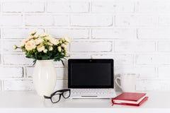 Lieu de travail avec l'ordinateur portable moderne au-dessus du mur de briques blanc Images libres de droits