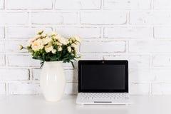 Lieu de travail avec l'ordinateur portable moderne avec l'écran vide au-dessus de la brique blanche Photos libres de droits