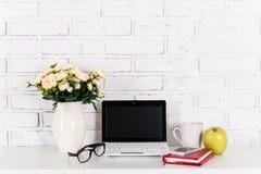 Lieu de travail avec l'ordinateur portable moderne sur la table au-dessus du mur de briques blanc Photo libre de droits