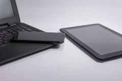 Lieu de travail avec l'ordinateur portable noir, la tablette et le téléphone intelligent sur le fond blanc Images libres de droits