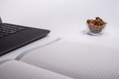 Lieu de travail avec l'ordinateur portable noir, le carnet et le raisin sec sur le fond blanc Images libres de droits