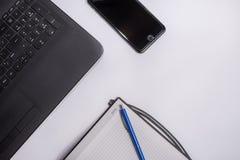 Lieu de travail avec l'ordinateur portable noir, le téléphone intelligent, le carnet et le stylo sur le fond blanc Photos stock