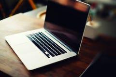 Lieu de travail avec l'ordinateur portable ouvert avec l'écran noir sur le bureau en bois moderne Image libre de droits