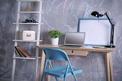Lieu de travail avec l'ordinateur portable sur la table dans la chambre Photos stock