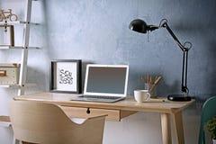 Lieu de travail avec l'ordinateur portable sur la table dans la chambre Photo libre de droits