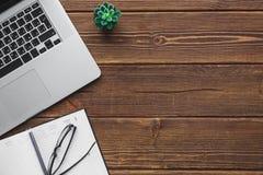 Lieu de travail avec l'ordinateur portable sur la table en bois Image stock