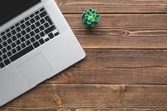 Lieu de travail avec l'ordinateur portable sur la table en bois Image libre de droits