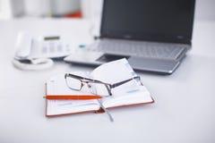 Lieu de travail avec la table de travail confortable d'ordinateur portable de carnet dans le bureau Photographie stock libre de droits