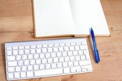 Lieu de travail avec la table de travail confortable d'ordinateur portable de carnet dans la vue de fenêtres et de ville de burea Image stock