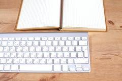 Lieu de travail avec la table de travail confortable d'ordinateur portable de carnet dans la vue de fenêtres et de ville de burea Images stock