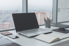 Lieu de travail avec la table de travail confortable d'ordinateur portable de carnet dans la vue de fenêtres et de ville de burea Images libres de droits