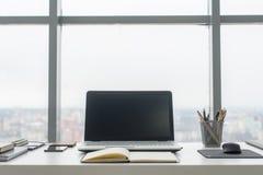Lieu de travail avec la table de travail confortable d'ordinateur portable de carnet dans la vue de fenêtres et de ville de burea Image libre de droits