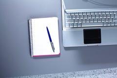 Lieu de travail avec la table de travail confortable d'ordinateur portable de carnet dans la vue de fenêtres et de ville de burea Photographie stock