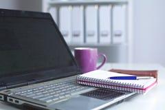 Lieu de travail avec la table de travail confortable d'ordinateur portable de carnet dans la vue de fenêtres et de ville de burea Photos libres de droits