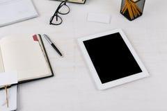 Lieu de travail avec la tablette blanche avec l'écran vide Image stock