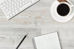 Lieu de travail avec la tasse du café, du clavier, du smarthphone, des feuilles blanches et du stylo sur la surface en bois dans  Images stock