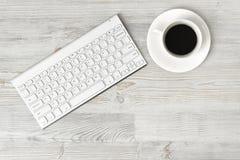 Lieu de travail avec la tasse du café et du clavier sur la surface en bois dans la vue supérieure Photographie stock libre de droits