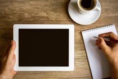 Lieu de travail avec la tasse numérique de comprimé, de carnet et de café Photos stock
