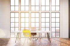 Lieu de travail avec le bureau blanc, une chaise de bureau et une chaise jaune transparente de visiteur Images libres de droits