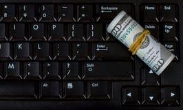 Lieu de travail avec le carnet d'argent - billets de banque de dollar US sur le clavier de l'ordinateur portable Facture roulée s photos stock