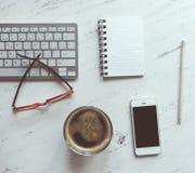 Lieu de travail avec le carnet, le café, le smartphone, les verres et keyboar Photographie stock libre de droits