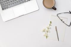 Lieu de travail avec le carnet vide, branche de jasmin de fleur, tasse Image libre de droits