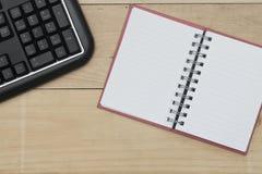 Lieu de travail avec le clavier, et le carnet sur la table Photo libre de droits