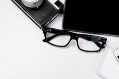 Lieu de travail avec le comprimé, le smartphone, le stylo, le bloc-notes et les verres Photographie stock