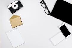 Lieu de travail avec le comprimé, le smartphone, le stylo, le bloc-notes et les verres Image stock