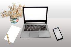 Lieu de travail avec le papier futé de téléphone d'écran blanc d'ordinateur portable et stylo d'isolement Photos libres de droits