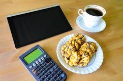 Lieu de travail avec le PC, la calculatrice, la tasse de café et les biscuits de comprimé Photographie stock libre de droits