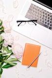 Lieu de travail avec le stylo et les pivoines de carnet en verre d'ordinateur portable Photos stock