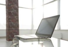 Lieu de travail de bureau avec l'ordinateur portable sur une table en verre dans un bureau moderne Photographie stock